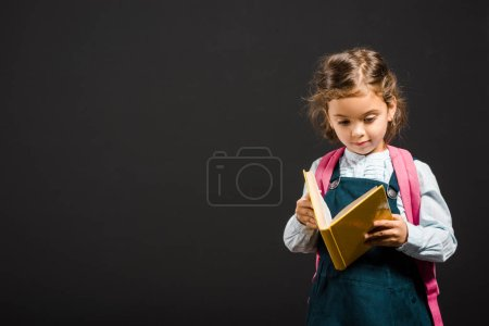 cute schoolgirl with backpack and book in hands isolated on black