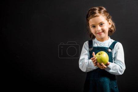 Photo pour Portrait d'écolière souriante avec pomme dans les mains isolées sur noir - image libre de droit