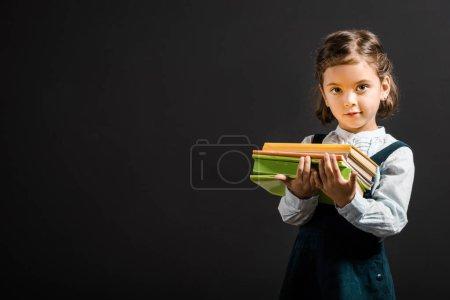 portrait of adorable schoolchild holding books isolated on black