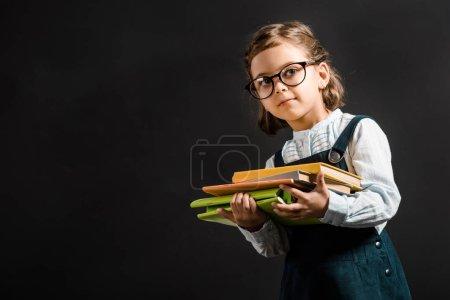Photo pour Portrait de l'adorable écolier en lunettes tenant des livres isolés sur noir - image libre de droit