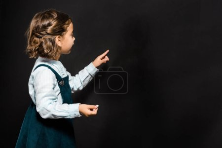 schoolchild with piece of chalk standing at blank blackboard