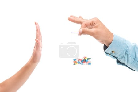cropped image of girl rejecting unhealthy drug pills and showing stop sign to man isolated on white
