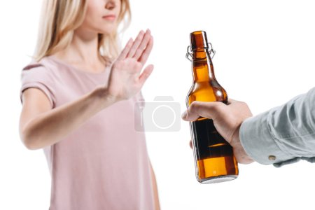 cropped image of blonde woman rejecting bottle of unhealthy beer isolated on white