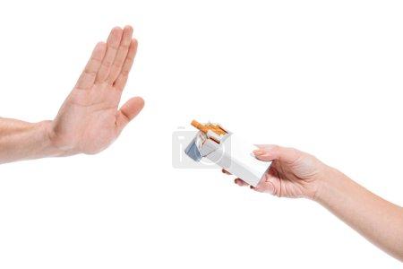 Photo pour Homme d'image recadrée rejetant le paquet de cigarettes de femme isolé sur blanc - image libre de droit