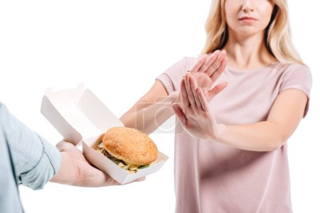 cropped image of woman rejecting unhealthy burger isolated on white