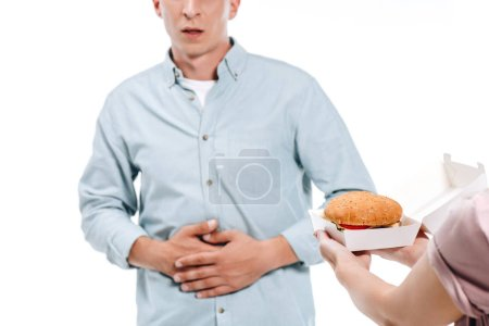 imagen recortada de hombre mostrando dolor de estómago a mujer proponiendo hamburguesa aislada en blanco
