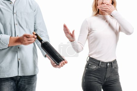 cropped image of woman covering mouth and rejecting bottle of red wine isolated on white