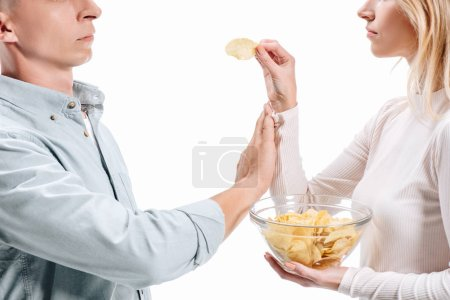 cropped image of man rejecting unhealthy potato chips from woman isolated on white