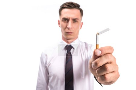 selective focus of businessman holding unhealthy broken cigarette isolated on white