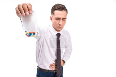 selective focus of businessman showing stomach pain and holding colored drug pills isolated on white