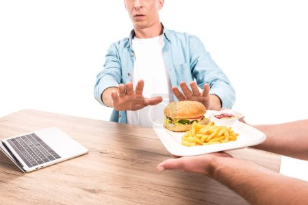 cropped image of man rejecting unhealthy burger and french fries at table isolated on white