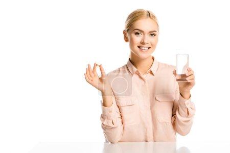 Photo pour Souriant verre tenue femme attirante de l'eau et pilule isolé sur blanc, en regardant la caméra - image libre de droit