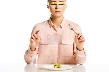 attractive woman with tape measure on eyes ready to eat broccoli isolated on white