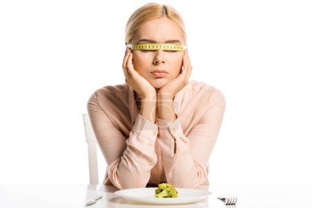 attractive woman with tape measure on eyes sitting near piece of broccoli on plate isolated on white