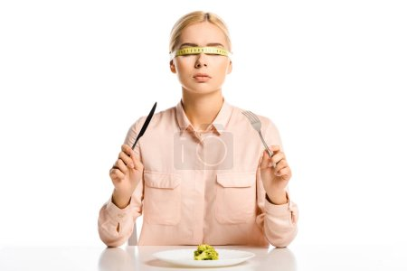 attractive woman with tape measure on eyes holding fork and knife, piece of broccoli on plate isolated on white