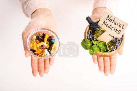 Foto de Imagen recortada de mujer sosteniendo cuencos con medicina natural aceite y pastillas farmacológicas aisladas en blanco - Imagen libre de derechos