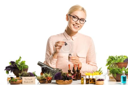 Photo for Smiling woman in glasses making essential oil isolated on white and looking at camera - Royalty Free Image