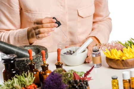cropped image of woman adding essential oil to natural medicines isolated on white
