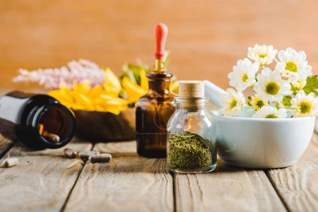 bottles of essential oils and herbs on wooden tabletop, alternative medicine concept