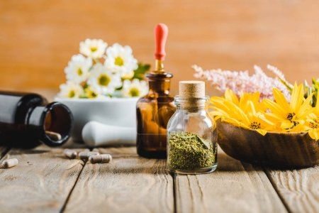 bottles of essential oils and blooming flowers on wooden tabletop, alternative medicine concept