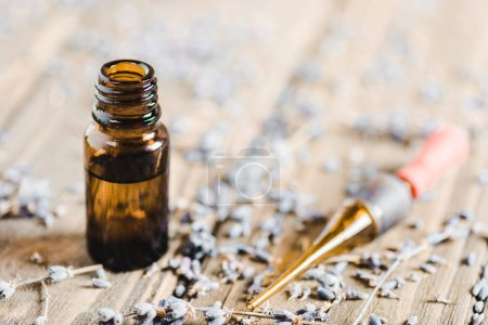 bottles of essential oil, dropper and scattered herbs on wooden tabletop, alternative medicine concept