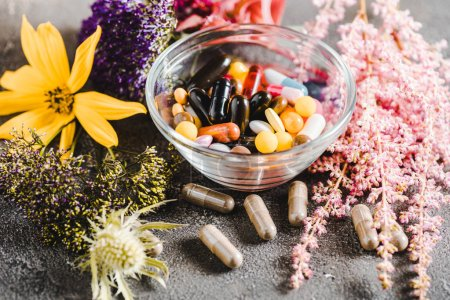 pharmacological pills and blooming flowers on wooden tabletop, alternative medicine concept