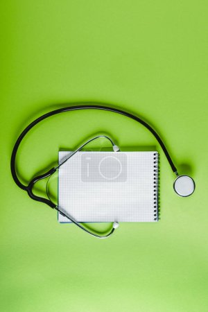 top view of stethoscope and empty notebook on green surface