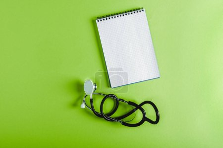 elevated view of stethoscope and empty notebook on green surface