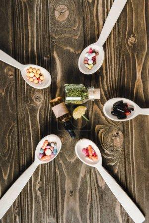 Photo pour Vue du dessus des cuillères avec des pilules et des bouteilles en verre avec des médicaments alternatifs sur table en bois - image libre de droit