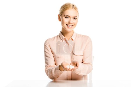 smiling blonde woman holding refined sugar and looking at camera isolated on white, diabetes concept