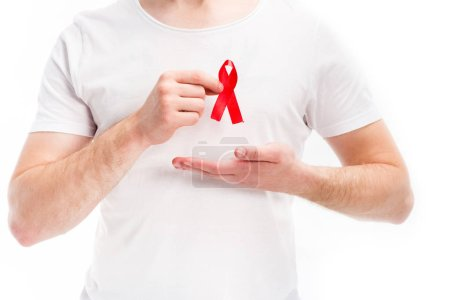 midsection of man showing red ribbon on shirt isolated on white, world aids day concept