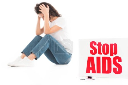 sad woman sitting and touching head isolated on white, stop aids card on foreground