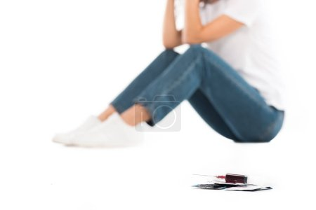 selective focus of woman sitting isolated on white, condoms and syringe with blood on foreground, world aids day concept