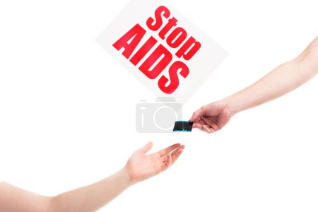cropped image of girlfriend giving condom to boyfriend, card with stop aids text isolated on white