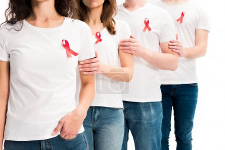 cropped image of people touching each other and standing with red ribbons on shirts isolated on white, world aids day concept