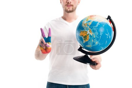 cropped image of man holding globe and showing peace sign with hand painted in rainbow isolated on white, world aids day concept