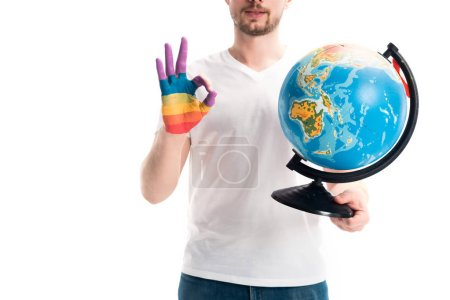 cropped image of man holding globe and showing okay gesture with hand painted in rainbow isolated on white, world aids day concept