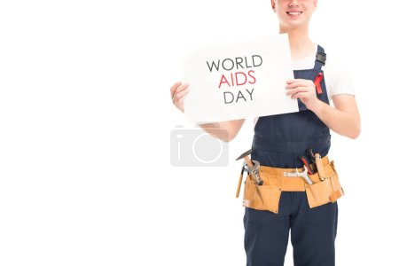 cropped image of smiling worker in uniform and red ribbon showing card with world aids day text isolated on white