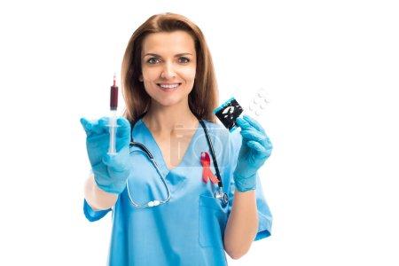 séduisante souriant médecin avec ruban rouge tenant la seringue avec du sang et des préservatifs avec les pilules isolé sur blanc, monde SIDA concept jour