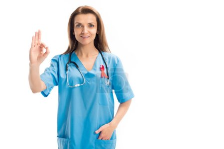 attractive doctor with red ribbon showing okay gesture isolated on white, world aids day concept
