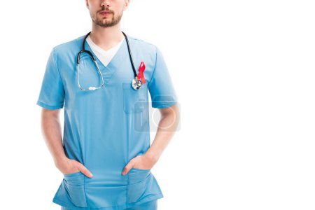 Cropped image de médecin permanent avec ruban rouge et stéthoscope isolé sur blanc, monde facilite la notion de jour