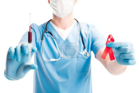 cropped image of doctor in medical mask holding red ribbon and syringe with blood isolated on white, world aids day concept