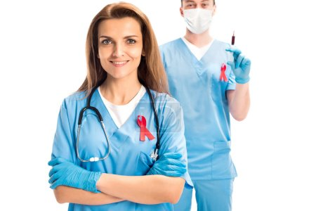 doctors standing with red ribbons and syringe isolated on white, world aids day concept