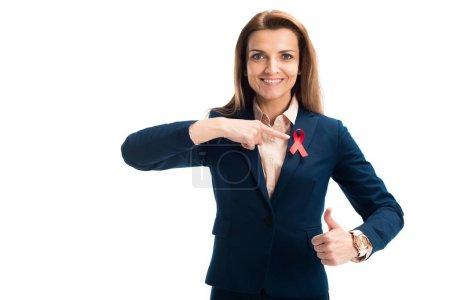 Foto de Sonriendo a empresaria atractiva apuntando en cinta roja y mostrando pulgar aislado en blanco, mundo SIDA día concepto de - Imagen libre de derechos