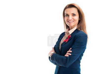 lächelnde attraktive Geschäftsfrau mit roter Schleife am Anzug, mit verschränkten Armen auf weißem, Welthilfetag-Konzept stehend