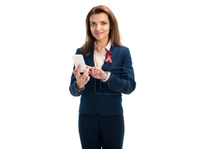 attractive businesswoman with red ribbon on suit using smartphone isolated on white, world aids day concept