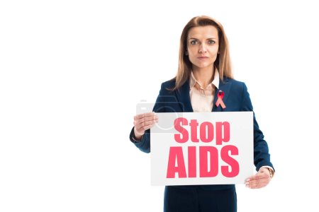 attractive businesswoman with red ribbon on suit showing card with stop aids text isolated on white