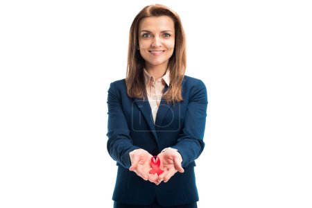attractive smiling businesswoman holding red ribbon in hands and looking at camera isolated on white, world aids day concept