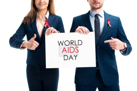 cropped image of businesspeople with red ribbons on suits pointing on card with world aids day text isolated on white