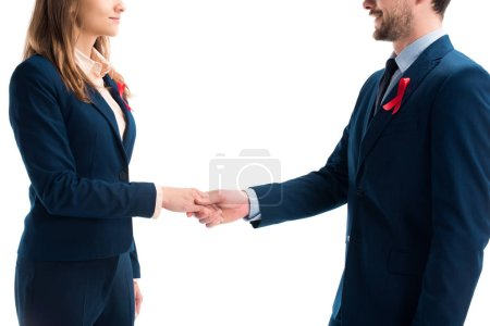cropped image of businesspeople with red ribbons on suits shaking hands isolated on white, world aids day concept